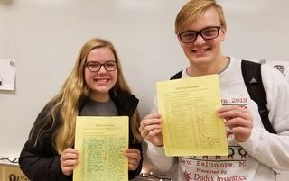 Girl and boy student holding yellow list of kindness acts