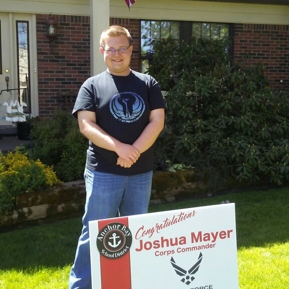 male student standing by sign in yard